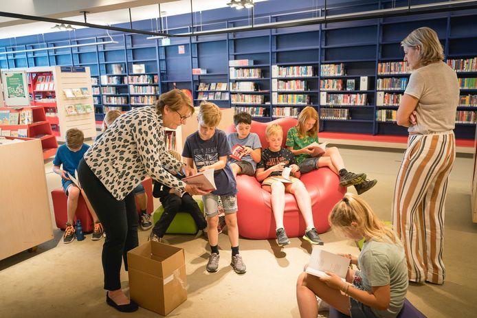 Directeur Alice Haak werpt met een van de leden van de digitale schoolkrant een blik in de gedichtenbundel van de G.J. van den Brinkschool. De andere kinderen doen hetzelfde. rechts José Tammer van de bblthk.
