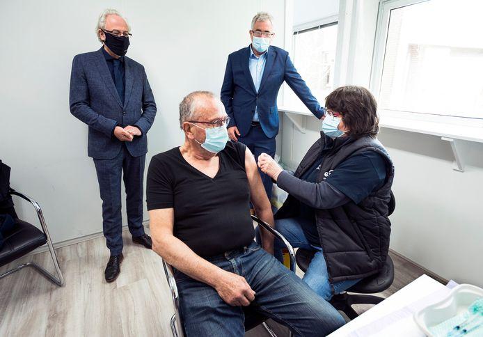 Burgemeester Victor Molkenboer (links) en zorgwethouder Arjan Noorthoek kijken hoe Henk Zonderman uit Oudewater een prik krijgt in het voormalige kantoor van Campina aan De Bleek.