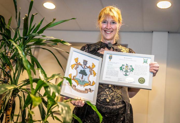 Ingrid Holtrust met haar familiewapen. Links de versie die ze zelf eerder bedacht en rechts de versie die officieel is geregistreerd bij de NGV.
