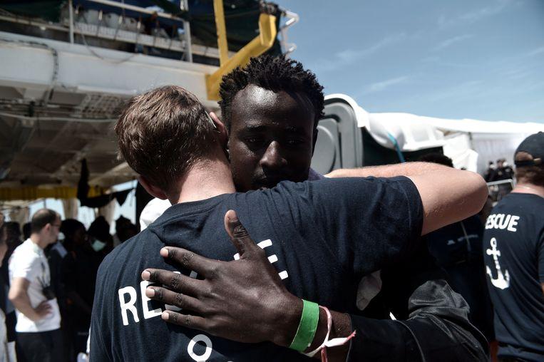 Een vluchteling krijgt nog snel een knuffel van een bemanningslid van de Aquarius voor hij aan landt gaat in Valencia. Beeld REUTERS