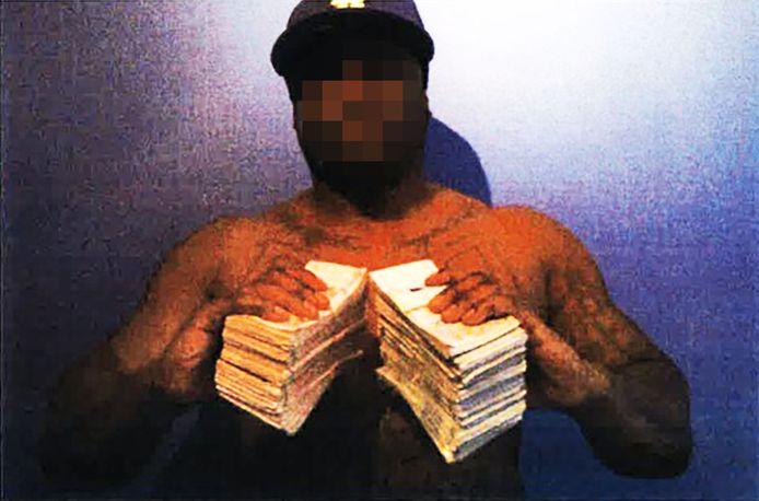 Delano R. poseert met grote pakken contant geld. De politie berekende dat hij in totaal 420.00 euro aan contanten bij zich had. Bovenstaande foto komt uit een politiedossier, waar deze site inzage in heeft gehad.