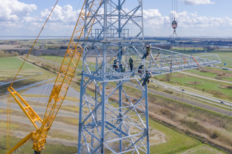 Het monteren van een zijarm, ofwel traverse, is een huzarenstukje. Deze grootste elektriciteitsmast van Zeeland is 98 meter hoog, bijna 44 meter breed en weegt 155.000 kilo. De funderingspalen (vier op elke hoek) zitten zo'n dertig meter in de grond.