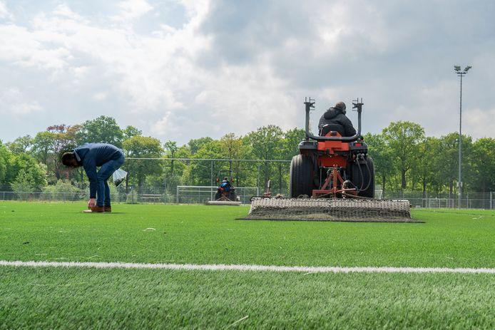Werkzaamheden bij de aanleg van het kunstgrasveld bij de Bredase voetbalvereniging JEKA. Later is dit veld afgekeurd voor gebruik vanwege de aanwezigheid van stukjes gals en metaal.