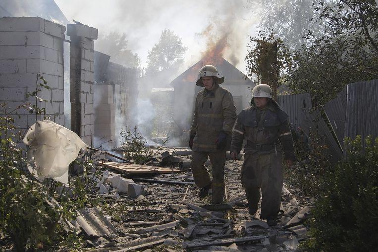 Brandweermannen lopen langs beschadigde gebouwen nabij het vliegveld in Donetsk, waar de afgelopen dagen hevig is gevochten. Beeld epa