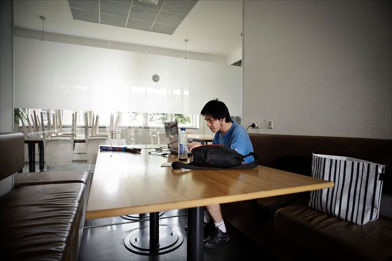 Een buitenlandse student gebruikt zijn laptop, en zit in zijn eentje in een werknis Beeld ANP