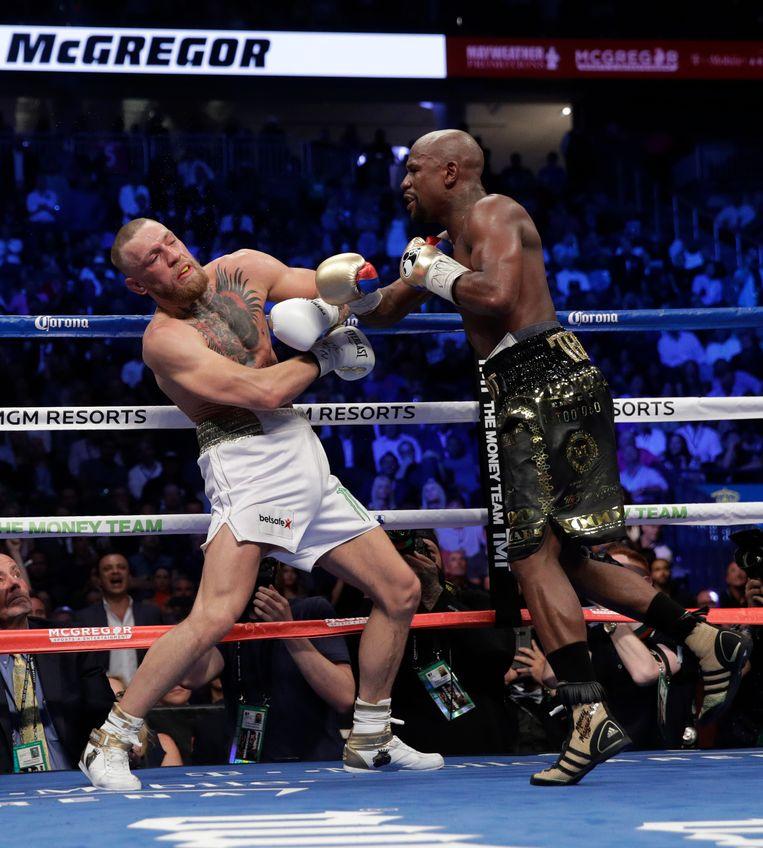 Floyd Mayweather Jr. hits Conor McGregor in a super welterweight boxing match Saturday, Aug. 26, 2017, in Las Vegas. (AP Photo/Isaac Brekken) Beeld AP