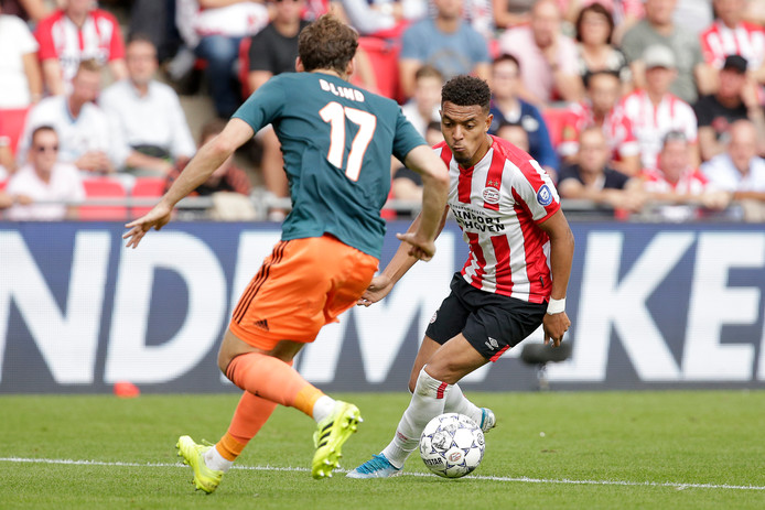 Donyell Malen (PSV, rechts) in duel met Daley Blind (Ajax)