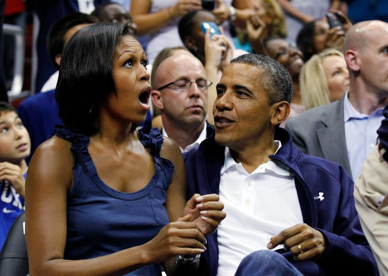 President Barack Obama, left, and first lady Michelle Obama, look up at themselves on the large in-house video screen as they appear on