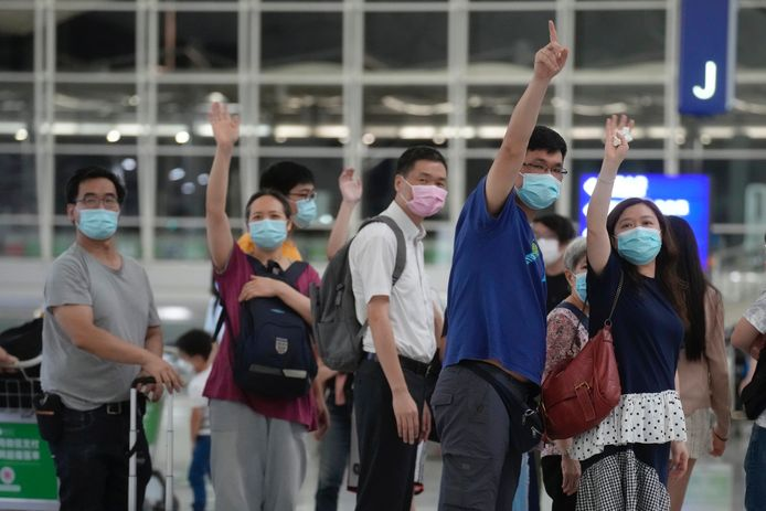 Hongkongers wuiven naar vrienden die emigreren naar Groot-Brittannië. Sinds de Britse regering die mogelijkheid biedt,  heeft een aantal bezorgde en kritische inwoners van de metropool gekozen voor een nieuw leven buiten China.