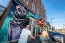 De kunstenares aan het werk in de De La Reystraat tijdens streetartfestival Pow Wow 2019. Het tweetal op de voorgrond kwam helemaal vanuit Hellevoetsluis naar Rotterdam fietsen om de muurschilderingen te bekijken.