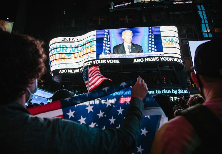 Mensen op Times Square kijken naar de speech van Biden. Beeld EPA