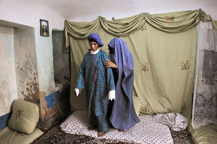Farzana ondernam een zelfmoordpoging nadat ze door haar schoonfamilie tot moes werd geslagen. Haar moeder helpt haar recht, op weg naar een ziekenhuis in Herat, 2010. Beeld © Lynsey Addario / 2021 The Atlantic Monthly Group, Inc.   All rights reserved. Distributed by Tribune Content Agency