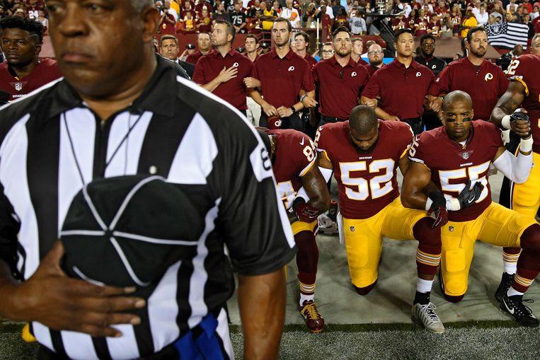 Een knielende Ryan Anderson #52 van de Washington Redskins met teamgenoten die eveneens knielen tijdens het spelen van het volkslied, eind vorig jaar voorafgaand aan de wedstrijd tegen de Oakland Raiders in Maryland.