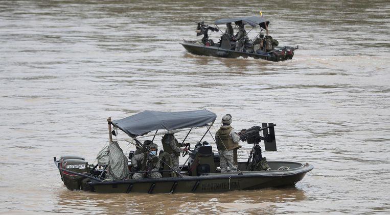 Colombiaanse militairen patrouilleren op de Arauca-rivier, de natuurlijke grens met Venezuela, eind maart.  Beeld Fernando Vergara / AP