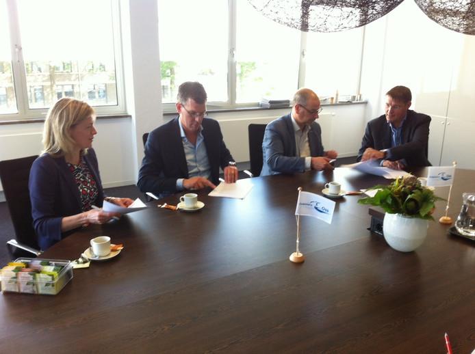Aan tafel Karin Wagemakers, Wim Muller, Gé Wagemakers en Lambèr Hendriks (vlnr) die een overeenkomst tekenen voor de laatste bouwfase van wijk Piekenhoef in Berghem.