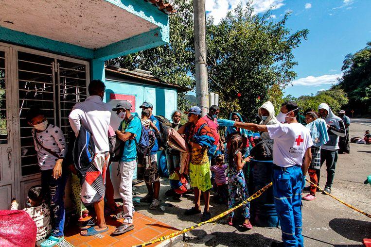 Venezolaanse migranten in de rij voor voedsel bij het Rode Kruis.  Beeld AFP