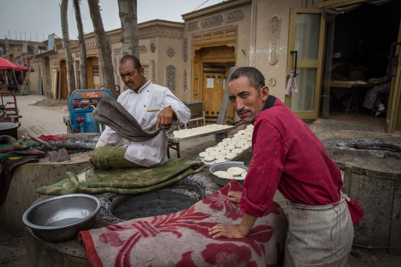 Lokale Oeigoeren bakken traditioneel brood op straat in de West-Chinese provincie Xinjiang.  Beeld LightRocket via Getty Images