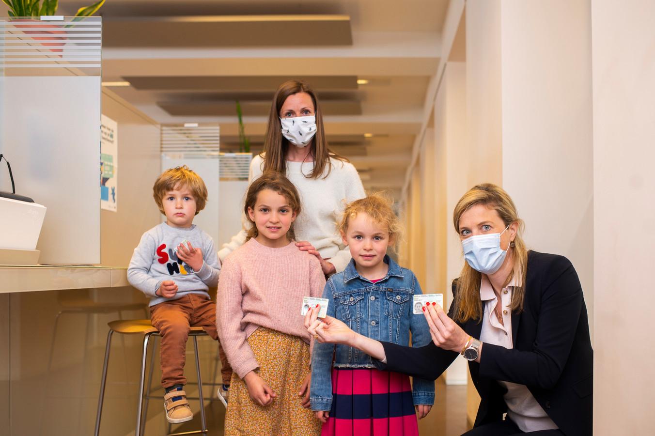 Minister Annelies Verlinden (CD&V) overhandigt de eerste exemplaren van de vernieuwde Kids-ID aan Felix (2), Emilia (8) en Roxanne (6)