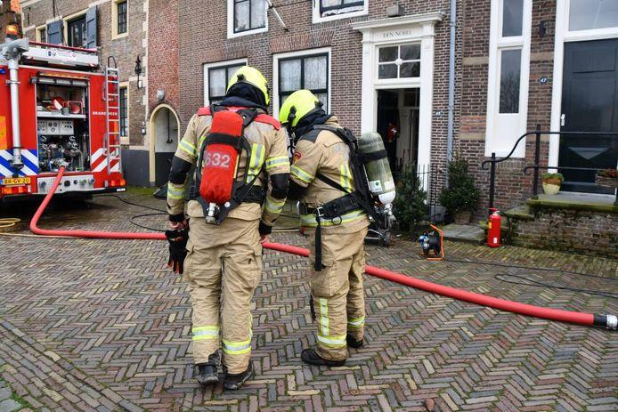 De brandweermannen staan voor de woning.
