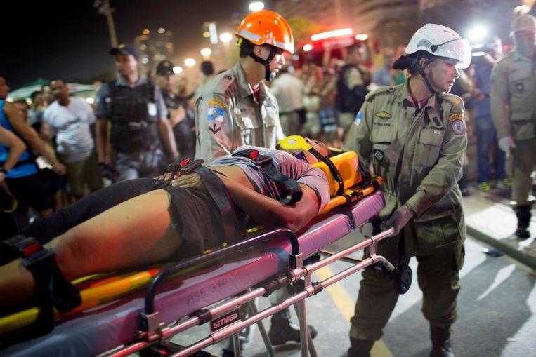 Een gewonde vrouw wordt afgevoerd.