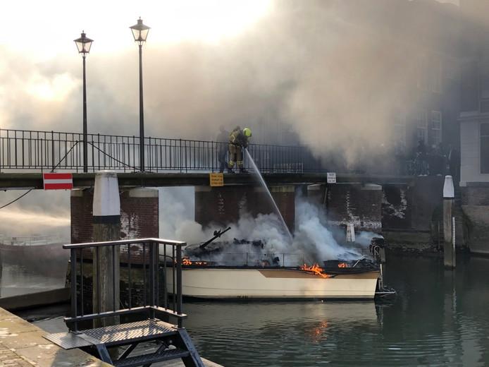 De brandweer blust de brand op het jacht dat onder de brug was gedreven.