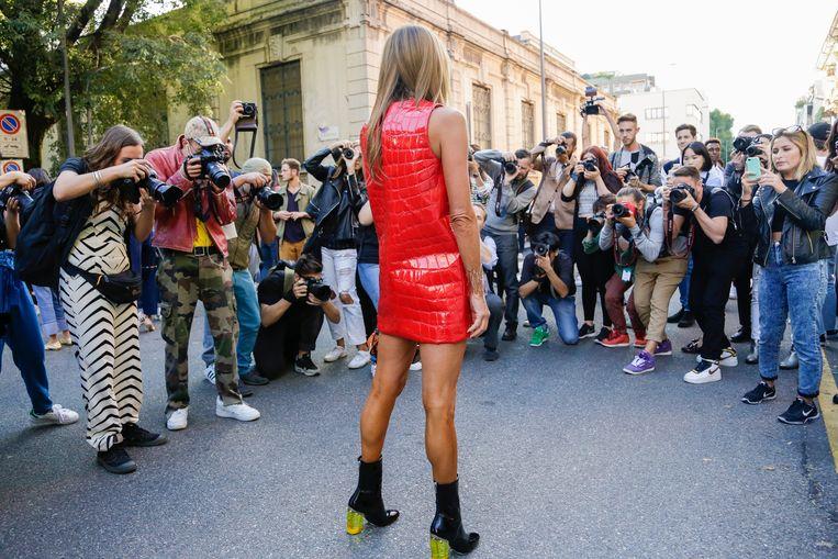 De invloedrijke Vogue-redacteur Anna Dello Russo arriveert bij een modeshow en wordt omringd door fotografen in Milaan (2015). Beeld