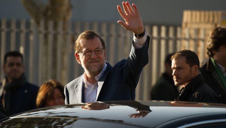 De Spaanse premier Mariano Rajoy zwaait nadat hij zijn stem heeft uitgebracht. Beeld getty