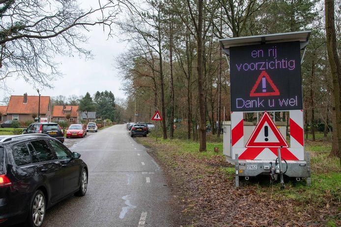 Een matrixbord waarschuwt voor drukte en auto's staan her en der langs de Bovenweg in Doornspijk geparkeerd.