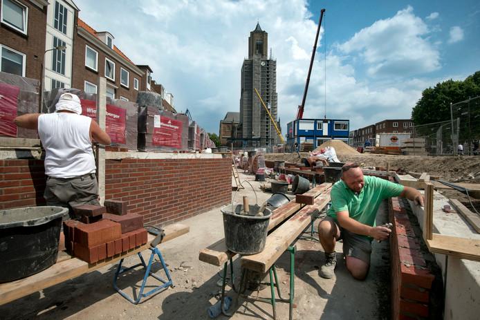 Werkzaamheden aan de Jansbeek. Wim Rohaan (rechts) uit Rijssen is aan het voegen.
