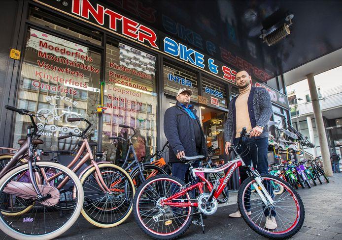 Ozan (rechts) en zijn vader Murat voor hun fietswinkel Inter Bikes aan de Hobbemastraat. ,,We verkopen vooral veel kinderfietsen.''