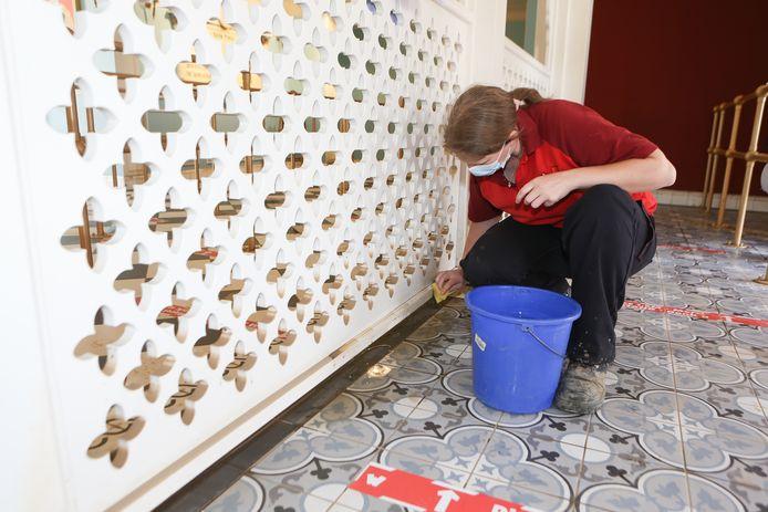 Alison nettoie les plinthes du Grand Maharajah Theatre avec un seau et une éponge.