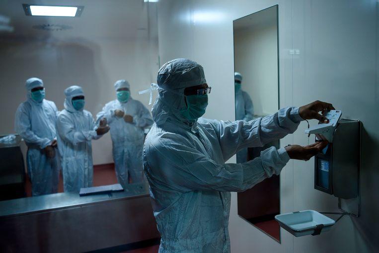 Wetenschappers maken zich klaar voor de productie van het AstraZeneca-vaccin in de Indiase metropool Poona. Beeld AFP