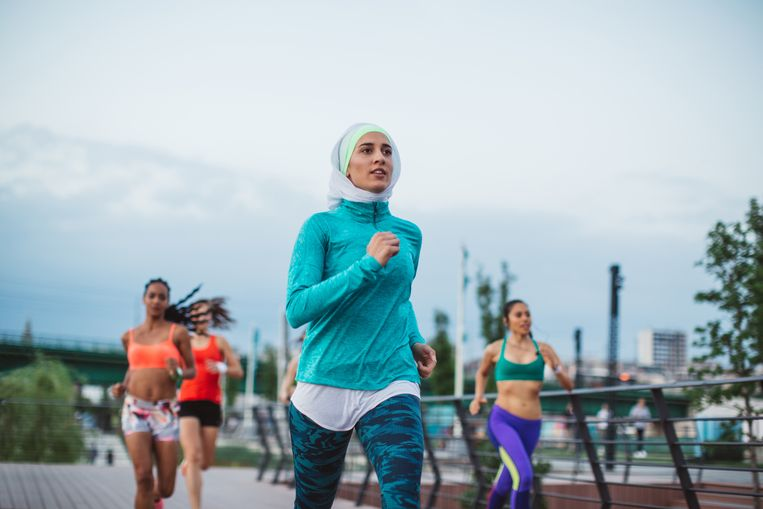 Veel Fransen zien de sporthidjab van Decathlon (inzet) als een onderwerping aan islamitische mode. De keten schrapt het artikel na alle protest. Beeld Getty Images