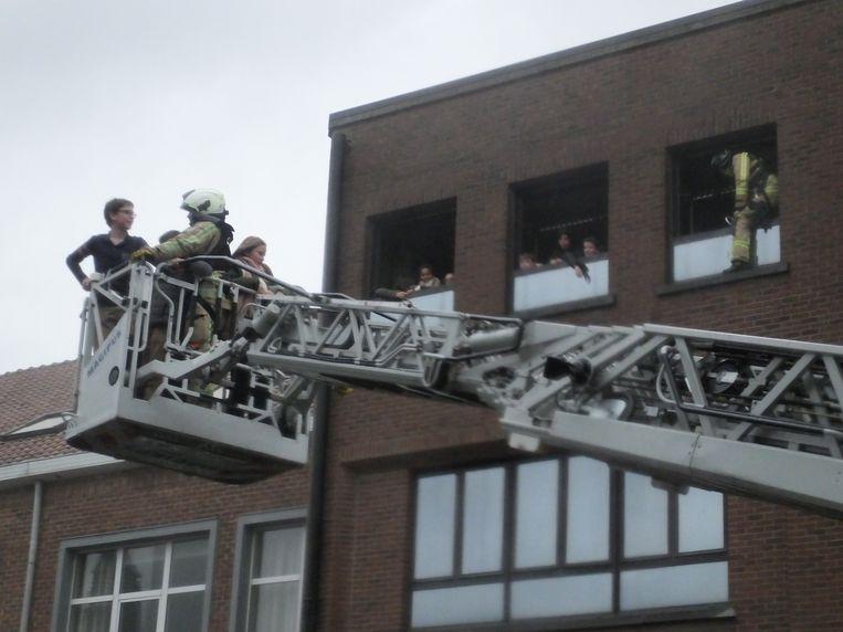 De leerlingen wordt met de ladderwagen uit het brandende schoolgebouw gered.