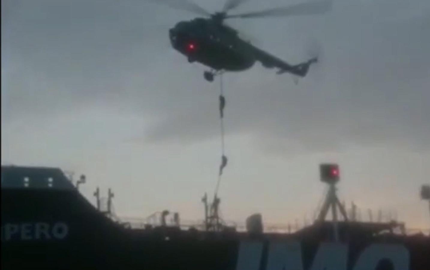 Leden van de garde laten zich uit een helikopter op het schip zakken.