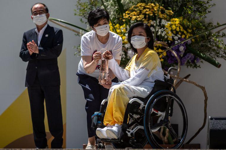 Voormalig paralympisch sporter en ambassadeur Aki Taguchi (rechts) en gouverneur van Tokio  Yuriko Koike (midden) tijdens de fakkelceremonie voorafgaand aan de opening. Beeld AFP