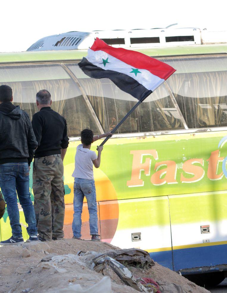 Een jongen wuift met de Syrische vlag terwijl een bus, ingehuurd door de Syrische regering, al-Islam rebellen evacueert uit Douma. Beeld EPA