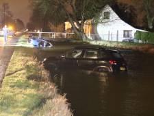 Man ramt politieauto en eindigt in sloot, naast auto die eerder in het water belandde
