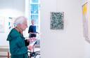 Een bezoeker van de expositie van kunstenaars Josée  Wuyts en Frans de Groot in Huis Kernhem leest de uitleg bij een van hun werken.
