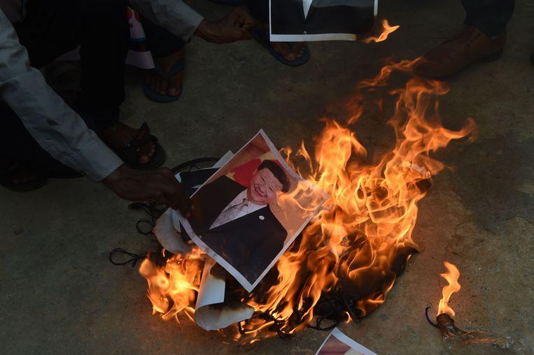 Indische activisten steken een foto van de Chinese leider Xi Jinping in brand. Beeld AFP