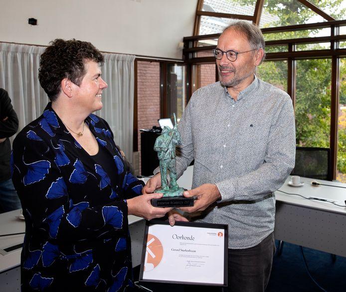 Molenaar Gerard Sturkenboom uit Heeze krijgt de Brabantse Molenprijs uit handen van commissaris van de Koning Ina Adema.