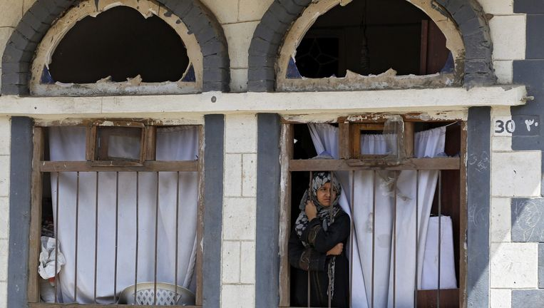 Een meisje uit Sanaa kijkt naar buiten vanuit haar huis dat is beschadigd door de bombardementen. Beeld epa