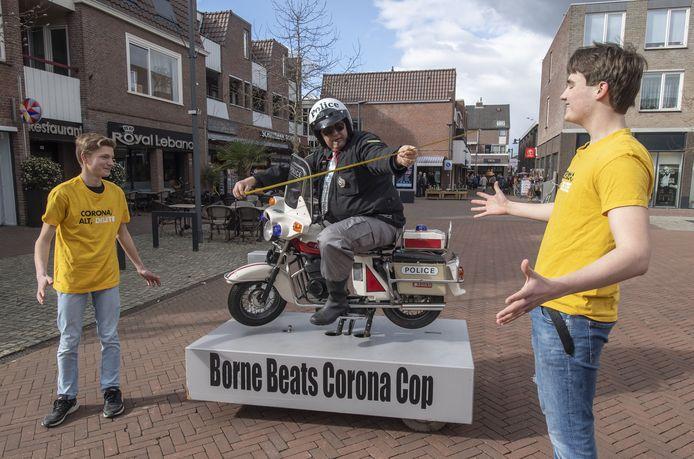 Borne heeft een echte 'coronacop'. Cabaretier Wim Ros gaat, uitgedost als heuse motoragent, drie dagen per week de binnenstad in om inwoners van Borne op ludieke manier te wijzen op coronamaatregelen tijdens het winkelen. Ideetje van scholieren Sem Mulder (links) en Wout Lubbers.