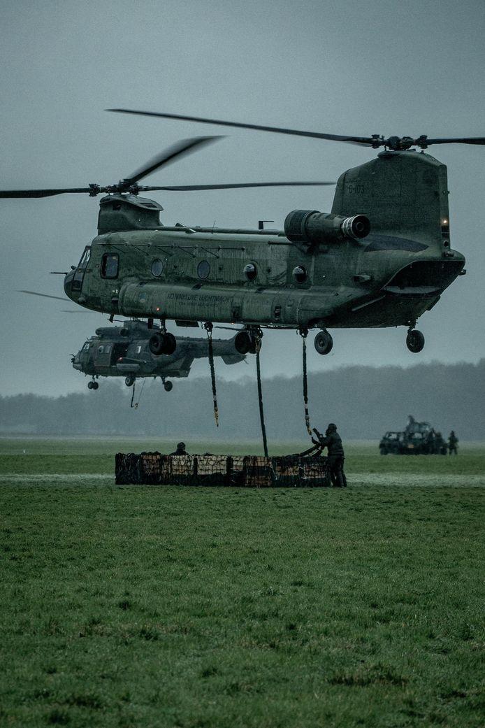 Een Chinook-helikopter pakt een lading op. Op de achtergrond een Cougar.