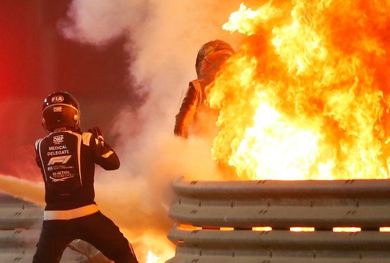 Romain Grosjean klimt uit zijn auto terwijl de vlammen hoog oplaaien. Beeld BSR Agency