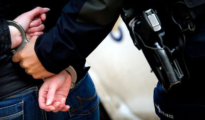GRONINGEN - Een politieagent voert een verdachte af. Aanhouding, arrestatie, handboeien, politie, agent, agenten. ANP XTRA KOEN VAN WEEL