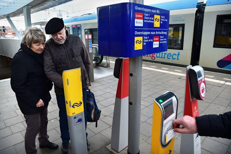 Twee reizigers stappen over op Arnhem CS. Beeld Marcel van den Bergh