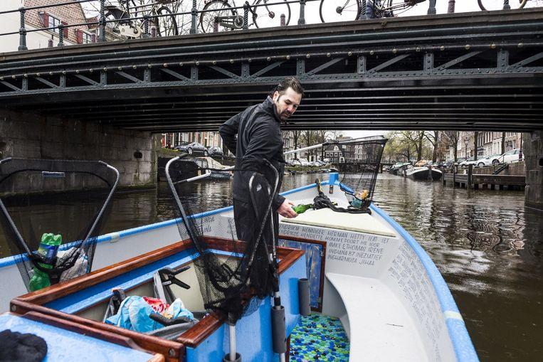 Het Amsterdamse bedrijf Plastic Whale haalt plastic petflesjes uit de gracht (in een plastic boot) voor het Belgische Ecover. Beeld Rink Hof