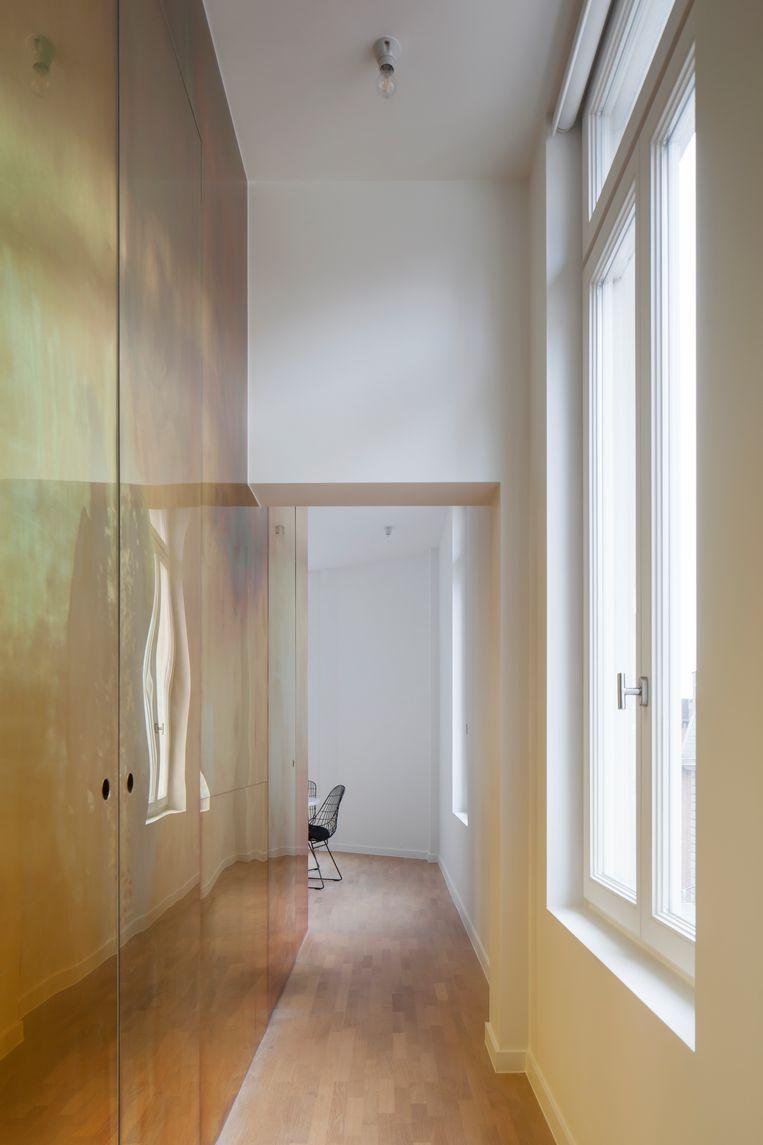 De binnenmuur evenwijdig met de buitengevel werd volledig bekleed met messing, een materiaal dat refereert aan het historische karakter van het gebouw. Onzichtbare deuren leiden naar de inkom, de keuken en de badkamer.   Beeld Johnny Umans