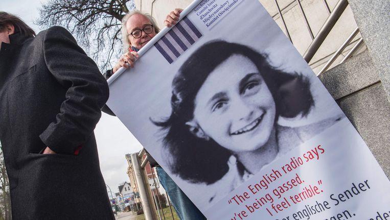 Activisten tonen voor het gerechtsgebouw affiches die aan de gruwel van de Holocaust herinneren. Beeld AFP